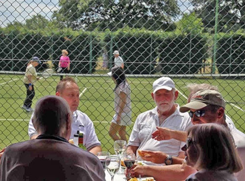 Stoke Poges Lawn Tennis Club members playing doubles and enjoying a drink and snack at the clubhouse