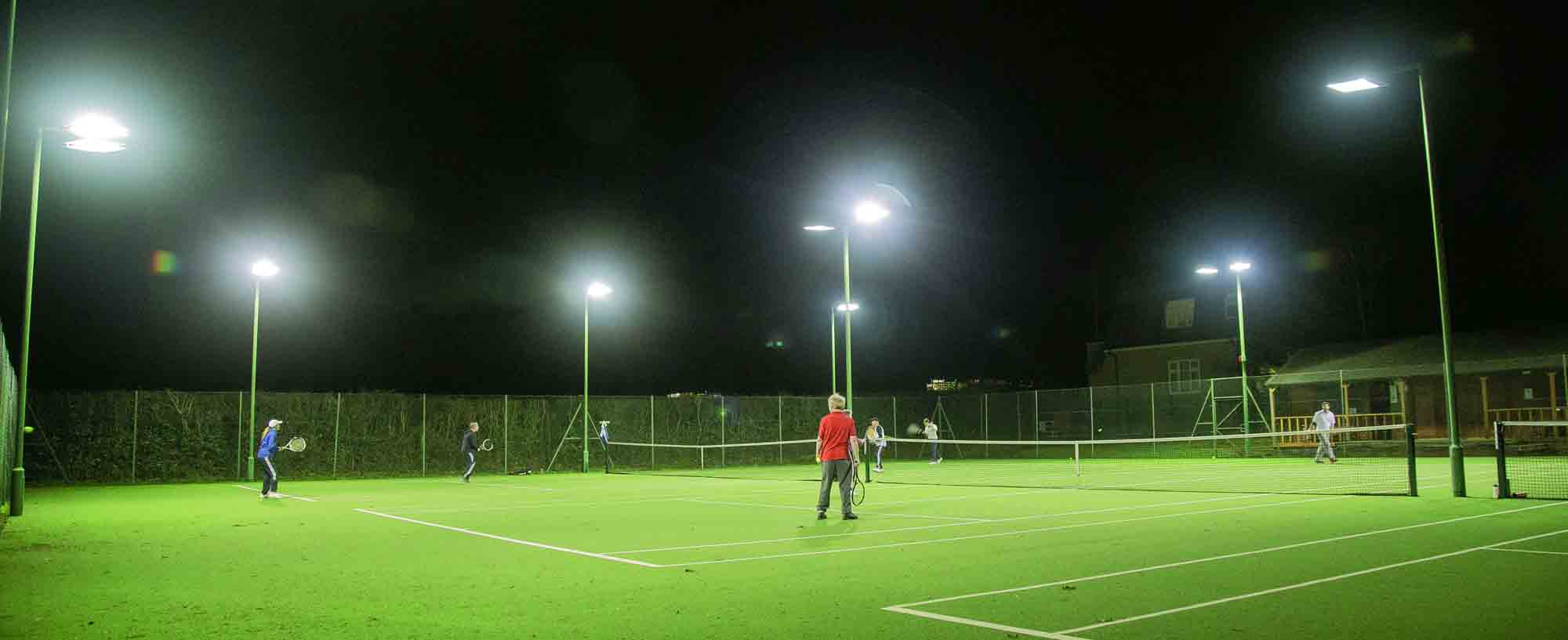 Floodlit tennis courts on a Thursday evening in Stoke Poges